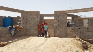 RS126679_IMGheader-AmmarKanaany_-MECH16-Kirkuk-May2016-family-in-front-of-a-structure-house